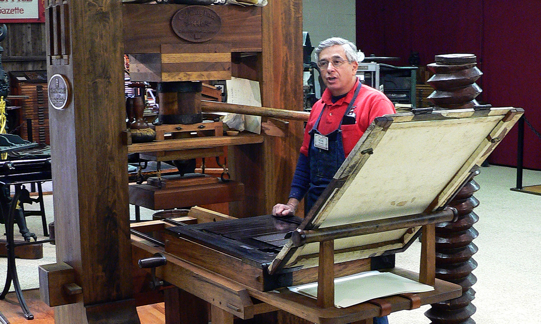 Peter Small demonstrating the use of the Gutenberg press at the International Printing Museum.